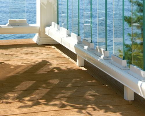Deckorators glass balusters installed on white deck rail with white connectors, close up