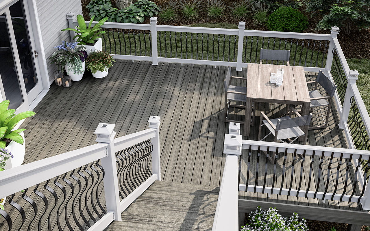 Heritage Smokehouse decking with white CXT Architectural railing, black Baroque balusters and white solar post caps.